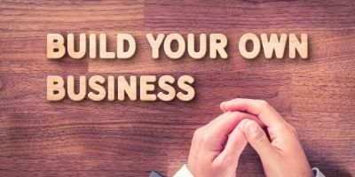"""hands folded near the words """"build your own business'"""